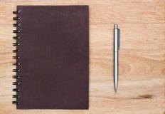 有笔的盖子笔记本在木背景 免版税图库摄影