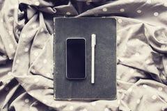 有笔的空白的智能手机屏幕和在小点围巾的黑日志 免版税库存图片