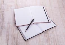 有笔的空白的笔记本在木头 库存图片