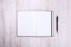 有笔的空白的笔记本在木头 免版税库存照片