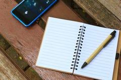 有笔的笔记本和在棕色长凳的手机 库存图片