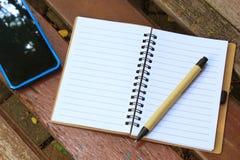 有笔的笔记本和在棕色长凳的手机 库存照片