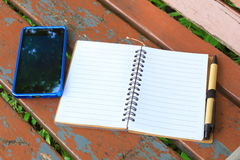 有笔的笔记本和在棕色长凳的手机 免版税库存照片