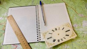 有笔的笔记本和时钟在背景中 库存照片