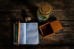 有笔的笔记本和灯笼老在老木书桌上 顶视图 库存照片