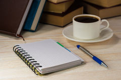 有笔的笔记本在窗口前面的一张木桌上 一个杯子在表的热咖啡 书查出在栈白色 免版税库存图片