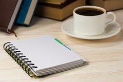 有笔的笔记本在窗口前面的一张木桌上 一个杯子在表的热咖啡 书查出在栈白色 库存照片