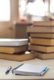 有笔的笔记本在窗口前面的一张木桌上 堆在桌上的书 免版税库存照片