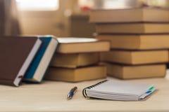有笔的笔记本在窗口前面的一张木桌上 水平的框架 库存图片