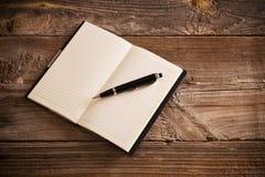 有笔的笔记本在老木桌上 免版税库存图片