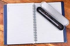 有笔的笔记本在老木桌上 库存照片