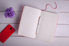 有笔的红色在白色背景的笔记本和智能手机 免版税库存图片
