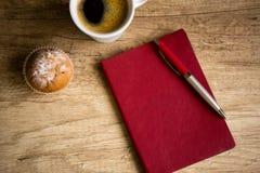有笔的红色笔记本在木桌上 免版税库存照片