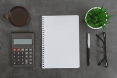 有笔记本、计算器、咖啡杯、镜片笔和盆的植物的工作书桌 图库摄影