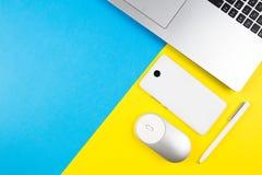 有笔记本、计算机老鼠、手机和白色笔的现代工作场所在蓝色和黄色颜色背景 库存照片