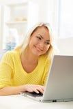 有笔记本个人计算机的美丽的白肤金发的女孩在家 免版税库存图片