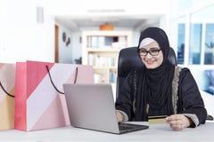 有笔记本和信用卡的阿拉伯妇女 免版税库存图片