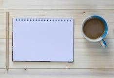 有笔记本和咖啡杯的一支铅笔在木背景 免版税库存图片