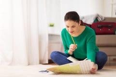 有笔记本和旅行地图的妇女在家 免版税图库摄影