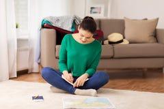 有笔记本和旅行地图的妇女在家 图库摄影