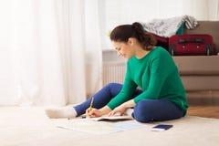 有笔记本和旅行地图的妇女在家 免版税库存图片