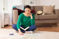 有笔记本和旅行地图的妇女在家 免版税库存照片
