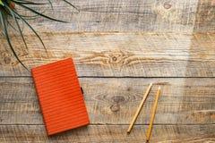 有笔记本和植物的运转的书桌 在阳光的木桌 免版税图库摄影
