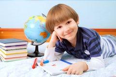 有笔记本和毛毡笔的微笑男孩 库存图片