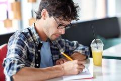 有笔记本和汁液文字的人在咖啡馆 免版税库存照片