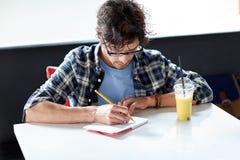 有笔记本和汁液文字的人在咖啡馆 免版税图库摄影