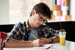 有笔记本和汁液文字的人在咖啡馆 库存照片