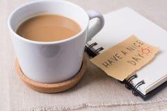 有笔记本和消息的,玩得高兴概念咖啡杯 免版税库存照片