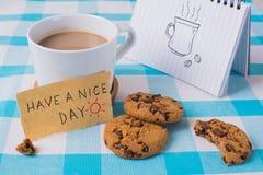 有笔记本和消息的,玩得高兴概念咖啡杯 库存图片