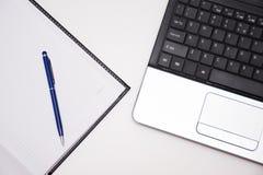 有笔记本和笔的计算机 免版税库存图片