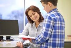 有笔记本和老师的男生在教室 免版税库存照片