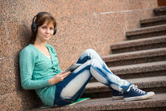 有笔记本和耳机的美丽的少妇学生 室外学员 免版税库存照片