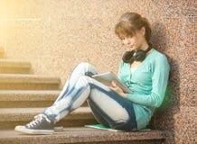 有笔记本和耳机的美丽的少妇学生 室外学员 免版税库存图片