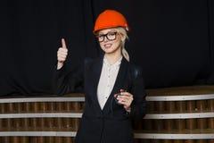 有笔记本和膝上型计算机的美丽的白肤金发的女实业家在橙色建筑盔甲和衣服的顶楼办公室 免版税库存图片