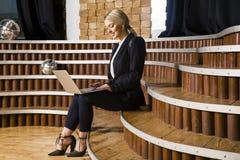 有笔记本和膝上型计算机的美丽的白肤金发的女实业家在顶楼办公室和衣服 库存图片