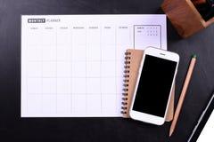 有笔记本和计划者日程表的黑屏智能手机 免版税库存照片