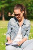 有笔记本文字的微笑的女孩在公园 免版税库存照片