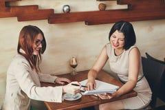 有笔记本的两名年轻微笑的白种人女实业家 咖啡馆的妇女 库存照片