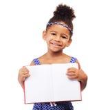 有笔记本的可爱的小女孩 库存照片