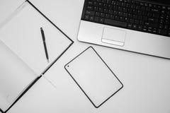 有笔记本的在书桌上的计算机和笔和片剂 免版税图库摄影