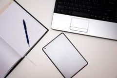 有笔记本的在书桌上的计算机和笔和片剂 免版税库存照片