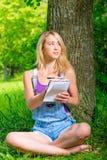 有笔记本的坐在树附近的金发碧眼的女人和笔 图库摄影