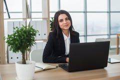 有笔记本的女商人在办公室,工作场所 库存照片