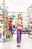 有笔记本的女孩在图书馆里站立在架子附近 免版税库存图片