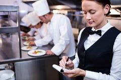 有笔记本的女服务员在商业厨房里 免版税库存照片