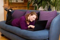 有笔记本的妇女在长沙发 库存图片